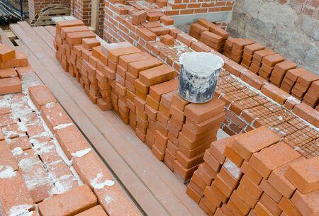 brick mason: Mason bricklaying background with bucket of clay brick blocks Stock Photo