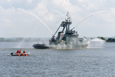 emit: Russia, St. Petersburg, July 15, 2015. Military Navy Training.. Fire ship water cannons emit a jet of water. Divers rescue sinking people.