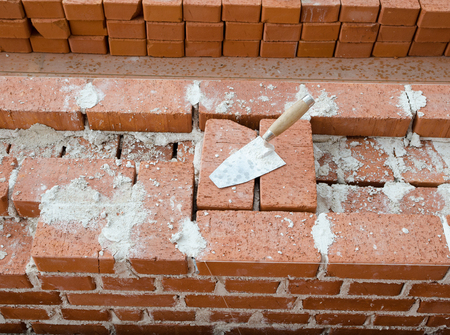 clay brick: Mason bricklaying background with trowel clay brick blocks Stock Photo