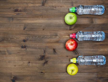 gordos: Concepto de estilo de vida saludable. tres manzanas de colores y botellas de agua del deporte en mesa de madera Foto de archivo