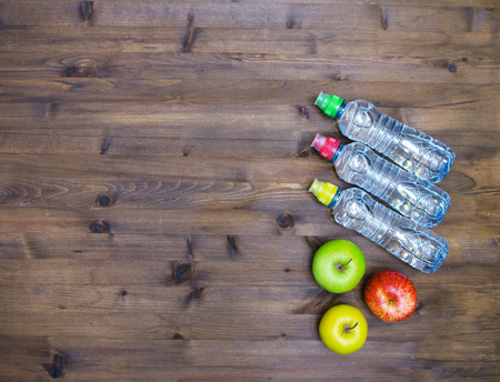 water bottles: Healthy lifestyle concept. three colored Apples and sport  water bottles on  wooden table