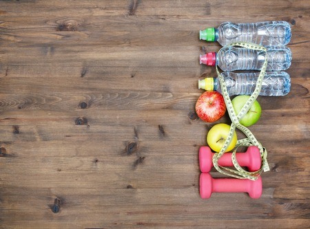 dumbbell: Healthy lifestyle concept. three colored Apples measuring tape dumbbells and sport  water bottles on  wooden table