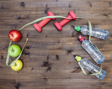 green energy: Healthy lifestyle concept. three colored Apples measuring tape dumbbells and sport  water bottles on  wooden table