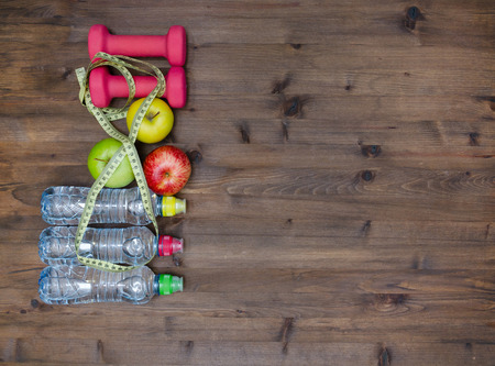 healthy sport: Healthy lifestyle concept. three colored Apples measuring tape dumbbells and sport  water bottles on  wooden table