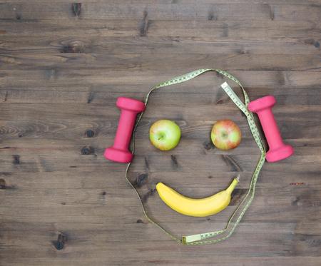 lifestyle: Zdrowe pojęcie życia. hantle kolorowe jabłka pomiarowe taśmy banana wyglądać twarz na drewnianym stole