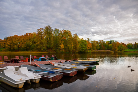 yellow boats: boats on the park pond. Autumn water landscape. Yellow leaves on trees. Stock Photo