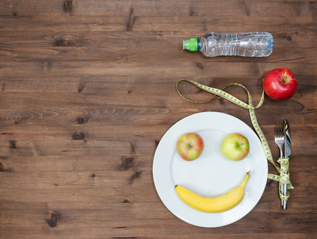 green eyes: Healthy lifestyle concept. colored Apples measuring tape dumbbells banana look like face sport  water on  wooden table Stock Photo