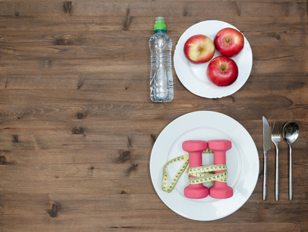 fat: Healthy lifestyle concept. colored Apples dumbbells and sport  water bottles on  wooden table Stock Photo