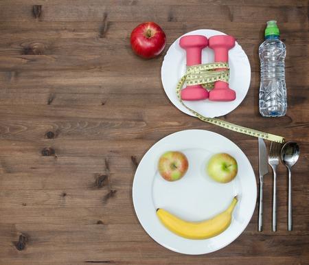 ojos verdes: concepto de estilo de vida saludable. Manzanas de colores que miden pesas de cinta de pl�tano se ven como el agua la cara del deporte en mesa de madera