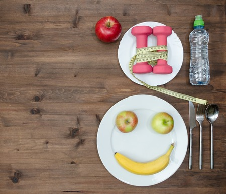 Healthy lifestyle concept. colored Apples measuring tape dumbbells banana look like face sport  water on  wooden table Standard-Bild