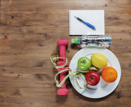 water bottle: Healthy lifestyle concept. Apples lemon orange measuring tape dumbbells sport water bottles and notebook on wooden table