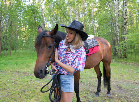 pet  animal: Beautiful woman  dressed in cowboy clothes stroking a brown horse