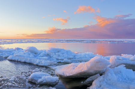 bluer: Ice melting on the beach in the sunset with open water in the background