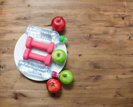 slim body: Healthy lifestyle concept. colored Apples dumbbells plate and sport water bottles on wooden table