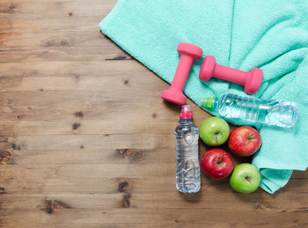 in towel: Healthy lifestyle concept. colored Apples dumbbells sport water bottles and turquoise towel on wooden table Stock Photo