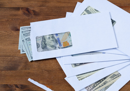 payola: American dollars in the envelopes on wooden table