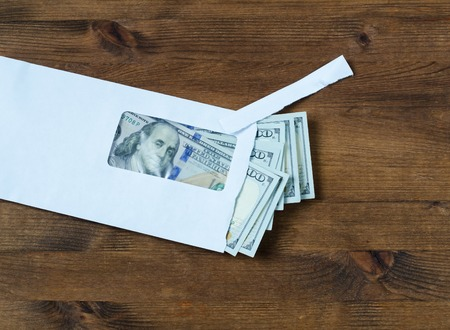batch of dollars: American dollars in the envelope on wooden table