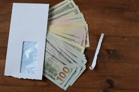 payola: American dollars and envelope on wooden table