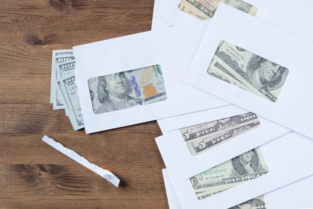 payola: American dollars in envelopes on wooden table