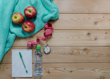 kilo: Healthy lifestyle concept. colored Apples notepad measure tape sport water bottle and turquoise towel on wooden table