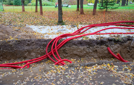 pipework: Plastic pipes containing electric cables, repair work in the park Stock Photo
