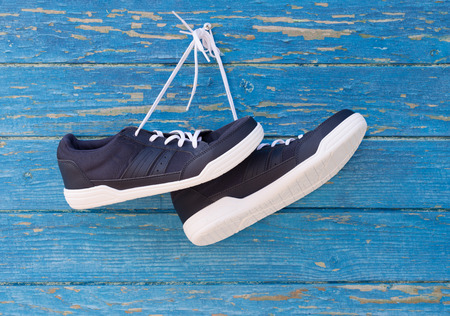 Blue sneakers hang on nail on colored wooden wall.