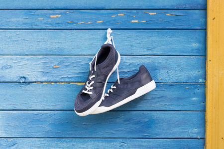 glamur: Blue sneakers hang on nail on colored wooden wall.