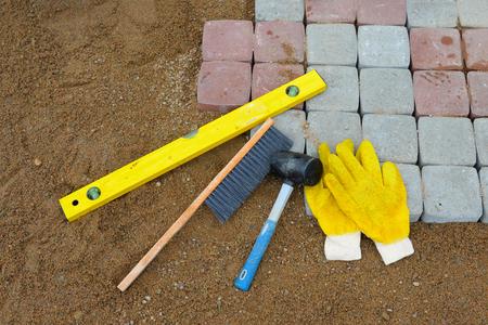 parapet: Pavement details, stone blocks rubber hammer level gloves and tape measure