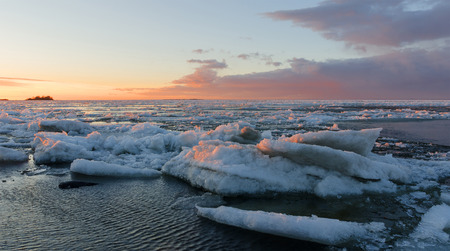 Ice melting on the beach in the sunset with open water