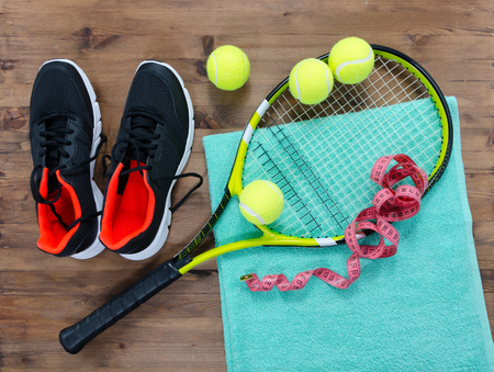 Tennis equipment set of racket balls sneakers and towel on wooden table