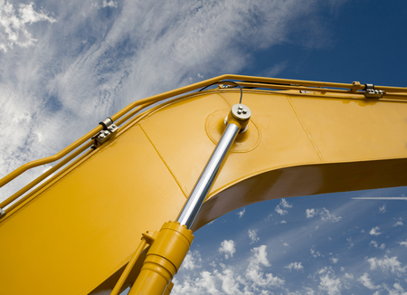 Detail of hydraulic bulldozer piston excavator arm on sky with clouds background Stock Photo