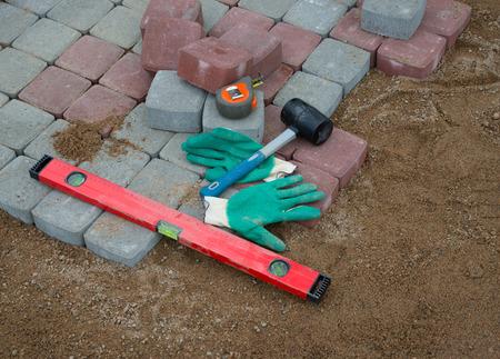 parapet: Pavement details stone blocks rubber hammer level gloves and tape measure Stock Photo