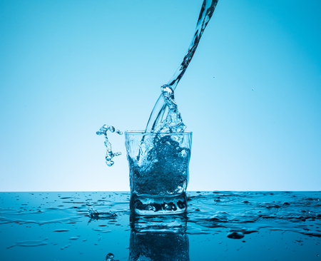 ?reative splashing water in the glass on blue background.