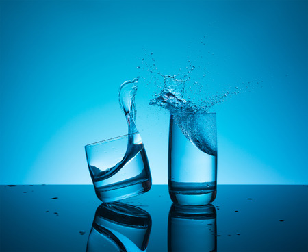 Ð¡reative splashing water in the glass on blue background.