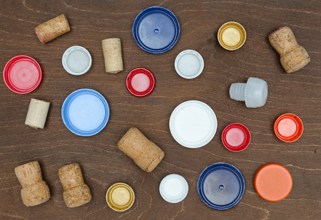 Composition with plastic caps and Wine corks background