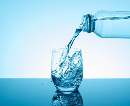 nourishing: Bottle with creative splashing water in the glass on blue background.