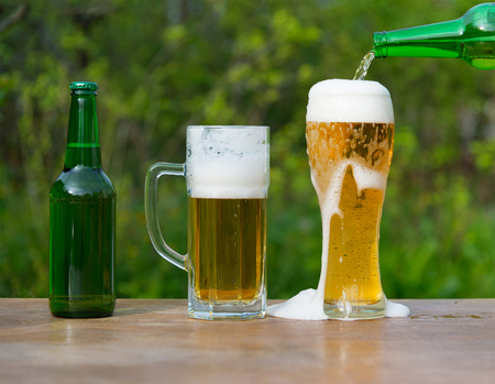 frothy: Pouring beer glasses from bottle on green background in the garden