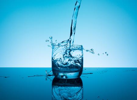 Salpicaduras creativas de agua en el vidrio sobre fondo azul. Foto de archivo - 80698137