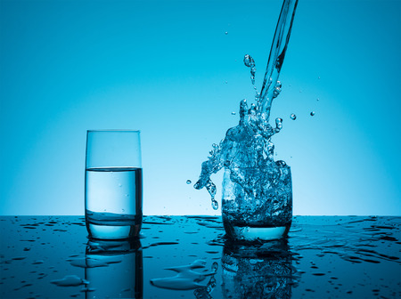 nourishing: Creative splashing water in the glass on blue background.