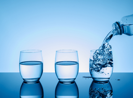 Creative splashing water in the glass on blue background