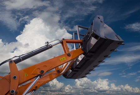 earthmover: Detail of hydraulic bulldozer piston excavator arm on sky with clouds background Stock Photo