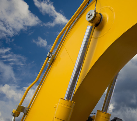 Detail of hydraulic bulldozer piston excavator arm on sky with clouds background Фото со стока