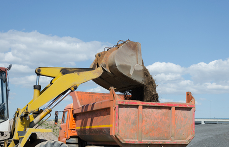 Wheel excavator loading gravel pile in the truck Stock Photo