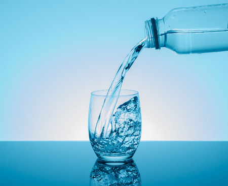 Creative splashing water in the glass on blue background. Stock Photo
