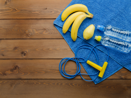 Fitness concept with skipping rope towel bottle of water pear and bananas on wooden table background Reklamní fotografie