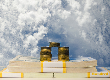 Stack of coin and Heap of one hundred dollar bills in packs on sky background Stock Photo