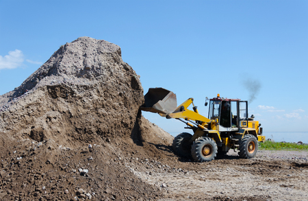 Wheel excavator digging  gravel pile for loading in the truck