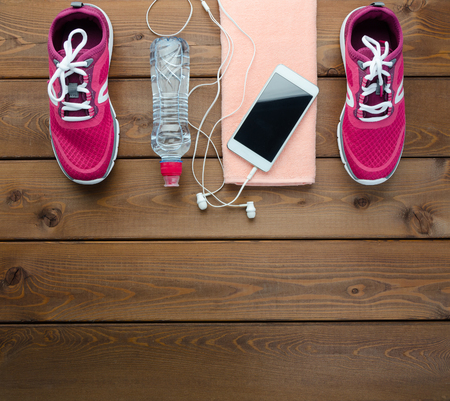 Fitness concept with sneakers smartphone and bottle of water on wooden table background