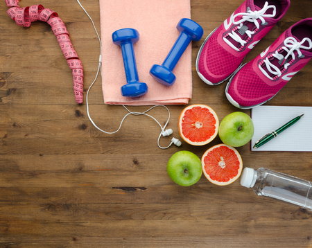 Fitness concept with sneakers dumbbells bottle of water apple and measure tape on wooden table background Stock Photo