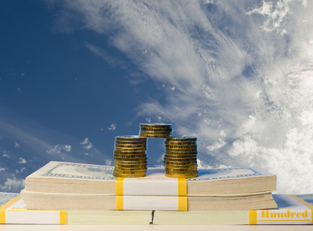 Stack of coin and heap of one hundred dollar bills in packs on cloudy sky background